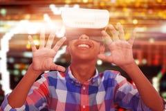 Imagen compuesta del muchacho feliz que mira a través del simulador de la realidad virtual mientras que se sienta en silla Imágenes de archivo libres de regalías