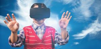 Imagen compuesta del muchacho joven en puente rojo con las auriculares de la realidad virtual Fotografía de archivo libre de regalías