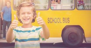 Imagen compuesta del muchacho que muestra los pulgares para arriba mientras que sonríe Imagenes de archivo