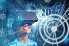 Imagen compuesta del niño pequeño que sostiene los vidrios virtuales y que mira lejos Imagen de archivo libre de regalías