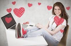 Imagen compuesta del pelirrojo bonito con los pies para arriba en el escritorio Imagen de archivo libre de regalías