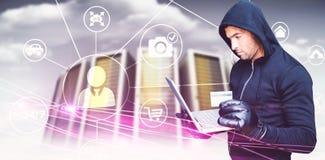 Imagen compuesta del pirata informático que sostiene la tarjeta del ordenador portátil y del credir Foto de archivo