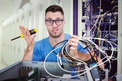 Imagen compuesta del retrato de confuso él profesional con destornillador y los cables delante del ope Imágenes de archivo libres de regalías