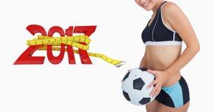 Imagen compuesta del retrato de la mujer feliz en ropa de deportes con fútbol Fotografía de archivo