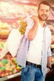 Imagen compuesta del retrato de las verduras que llevan del hombre joven en panier Imagen de archivo