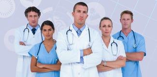 Imagen compuesta del retrato de los doctores serios que se colocan con los brazos cruzados Fotografía de archivo