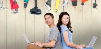 Imagen compuesta del retrato de pares felices jovenes usando el ordenador portátil mientras que se sienta Fotos de archivo