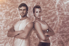 Imagen compuesta del retrato de un par deportivo con los brazos cruzados Fotografía de archivo libre de regalías