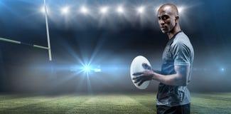 Imagen compuesta del retrato del atleta confiado que se coloca con la bola de rugbi Imagen de archivo libre de regalías