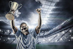 Imagen compuesta del retrato del deportista feliz que anima mientras que sostiene el trofeo Foto de archivo