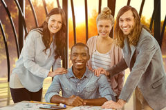 Imagen compuesta del retrato del equipo sonriente del negocio que pone las manos en hombro del hombre en el escritorio foto de archivo libre de regalías