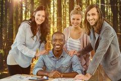 Imagen compuesta del retrato del equipo sonriente del negocio que pone las manos en hombro del hombre en el escritorio fotos de archivo libres de regalías