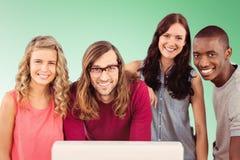 Imagen compuesta del retrato del equipo sonriente del negocio que se coloca en el escritorio del ordenador fotografía de archivo