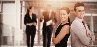 Imagen compuesta del retrato del hombre de negocios y de la mujer de negocios que presentan detrás contra la parte posterior imagenes de archivo
