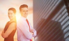 Imagen compuesta del retrato del hombre de negocios y de la mujer de negocios que presentan detrás contra la parte posterior fotos de archivo libres de regalías