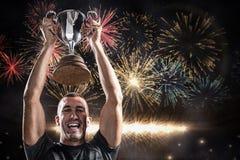 Imagen compuesta del retrato del jugador acertado del rugbi que celebra el trofeo fotografía de archivo