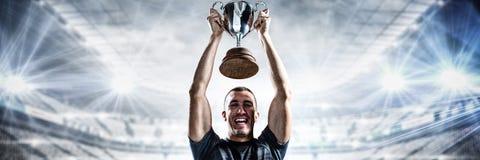 Imagen compuesta del retrato del jugador acertado del rugbi que celebra el trofeo imagen de archivo