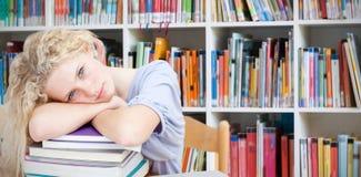 Imagen compuesta del teeenager cansado que duerme en una biblioteca Fotos de archivo