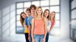 Imagen compuesta del tiro integral de un grupo sonriente que se coloca detrás de uno otro a los diversos ángulos Fotos de archivo