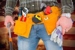 Imagen compuesta del trabajador manual que sostiene guantes y el martillo Imágenes de archivo libres de regalías