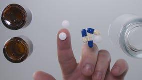 Imagen con las manos del hombre que toman algunas píldoras de la medicina de la superficie del vidrio de la tabla foto de archivo