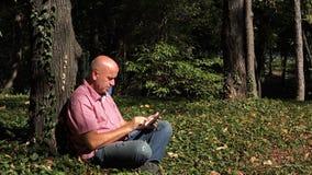 Imagen con un hombre de negocios relajado en el parque que manda un SMS usando red inalámbrica del teléfono móvil foto de archivo
