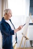 Imagen concentrada de la pintura del hombre mayor en el caballete en casa fotos de archivo
