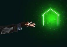 Imagen conceptual con la mano que señala en el icono de la casa o de la página principal en fondo oscuro Imagen de archivo