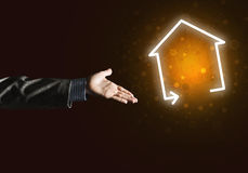 Imagen conceptual con la mano que señala en el icono de la casa o de la página principal en fondo oscuro Imagenes de archivo