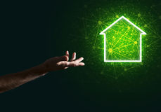 Imagen conceptual con la mano que señala en el icono de la casa o de la página principal en fondo oscuro Fotografía de archivo libre de regalías
