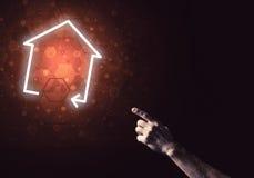 Imagen conceptual con la mano que señala en el icono o de la casa o de la página principal Fotos de archivo libres de regalías