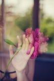 Imagen conceptual de la mujer joven que sostiene la flor de la peonía imagenes de archivo