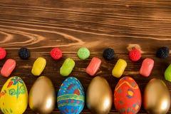 Imagen conceptual de Pascua con los huevos y color cendy en fondo de madera Imagen de archivo libre de regalías