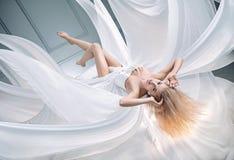 Imagen conceptual de un blonde que eleva y mantiene flotando foto de archivo