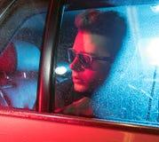Imagen conceptual de un hombre hermoso que se sienta en el coche Foto de archivo libre de regalías