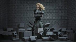 Imagen conceptual de una señora rubia entre muchas cajas Fotos de archivo