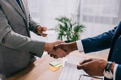 Imagen cosechada de dos hombres de negocios que sacuden las manos y que dan tarjetas de la visita a imagen de archivo libre de regalías