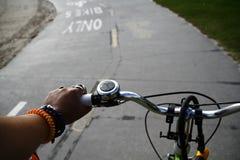Imagen cosechada de la bicicleta humana del montar a caballo de la mano con la marca de camino Fotografía de archivo libre de regalías