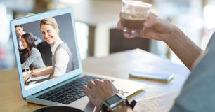 Imagen cosechada de la comunicación video de la persona en el ordenador portátil mientras que comiendo café foto de archivo libre de regalías