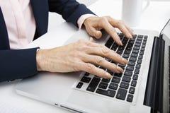 Imagen cosechada de la empresaria mayor que mecanografía en el ordenador portátil imagen de archivo libre de regalías