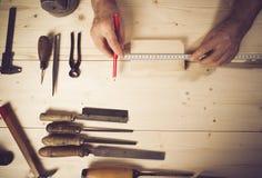 Imagen cosechada de la madera de medición del carpintero mayor en taller Fotografía de archivo libre de regalías