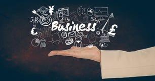 Imagen cosechada de la mano que se sostiene que lleva a cabo el texto del negocio en medio de diversos iconos Foto de archivo libre de regalías