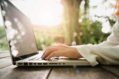 Imagen cosechada de la mujer joven que usa el ordenador portátil en la cafetería Ciérrese encima de la mujer asiática del retrato Fotografía de archivo libre de regalías