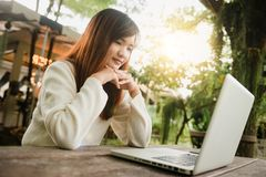 Imagen cosechada de la mujer joven que usa el ordenador portátil en la cafetería Ciérrese encima de la mujer asiática del retrato Fotos de archivo