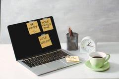 Imagen cosechada de la mujer que lleva a cabo la etiqueta engomada del papel con ideas de la palabra cerca del ordenador portátil imagen de archivo