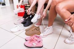 Imagen cosechada de los adolescentes que intentan en los zapatos de los deportes en una tienda Imagen de archivo libre de regalías