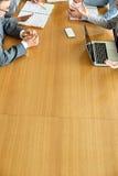 Imagen cosechada de los empresarios que discuten en la mesa de reuniones Imagen de archivo