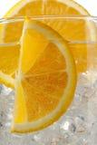 Imagen cosechada de rebanadas anaranjadas con los cubos de hielo. imagen de archivo