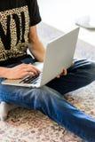 Imagen cosechada de un hombre joven que trabaja en el ordenador que se sienta en la tabla de madera imagen de archivo