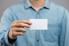 Imagen cosechada de un hombre que sostiene la tarjeta de visita blanca imagen de archivo
